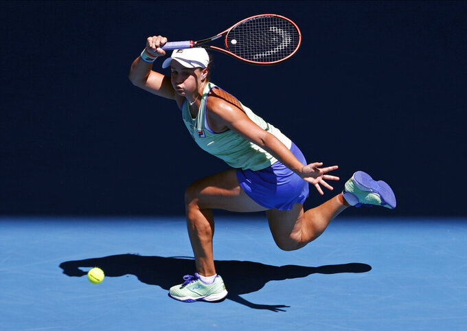 FILE - In this Jan. 30, 2020, file photo, Australia's Ashleigh Barty makes a forehand return to Sofia Kenin of the U.S. during their semifinal match at the Australian Open tennis championship in Melbourne, Australia. The heads of the ATP and WTA professional tennis tours tell the AP that they are coordinating with each other as they weigh how to reschedule the sport's calendar for whenever play can resume after the COVID-19 pandemic. (AP Photo/Andy Wong, File)