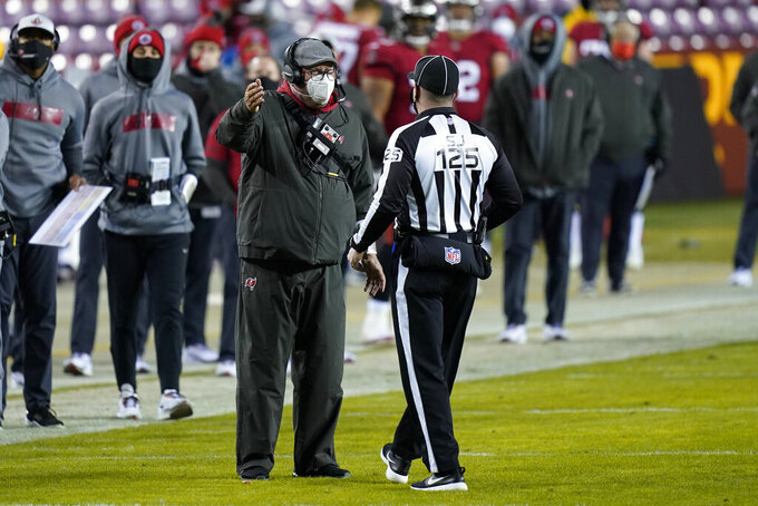 Tampa Bay Buccaneers head coach Bruce Arians talks with side judge Chad Hill (125) during the first half of the team's NFL wild-card playoff football game against the Washington Football Team, Saturday, Jan. 9, 2021, in Landover, Md. (AP Photo/Al Drago)