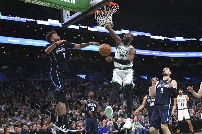 Boston Celtics guard Jaylen Brown (7) dunks next to Orlando Magic guard Michael Carter-Williams, left, during the fourth quarter of an NBA basketball game in Boston, Wednesday, Feb. 5, 2020. (AP Photo/Charles Krupa)