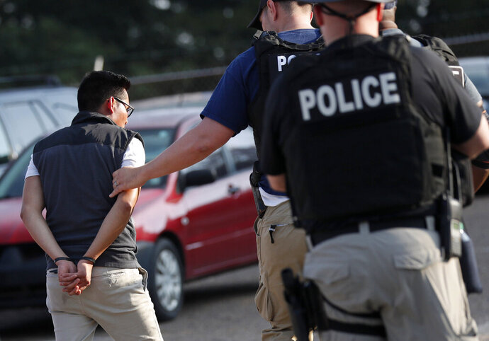 FILE - In this Aug. 7, 2019, file photo, a man is taken into custody at a Koch Foods Inc. plant in Morton, Miss. Unauthorized workers are jailed or deported, while the managers and business owners who profit from their labor often aren't. Under President Donald Trump, the numbers of owners and managers facing criminal charges for employing unauthorized workers have stayed almost the same. (AP Photo/Rogelio V. Solis, File)