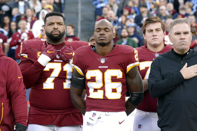 FILE - In this Dec. 22, 2018, file photo, Washington Redskins running back Adrian Peterson (26) stands for the national anthem before an NFL football game against the Tennessee Titans in Nashville, Tenn. NFL players who want to kneel during the national anthem to protest police brutality and racism have far more support than Colin Kaepernick did  four years ago.  (AP Photo/Mark Zaleski, File)