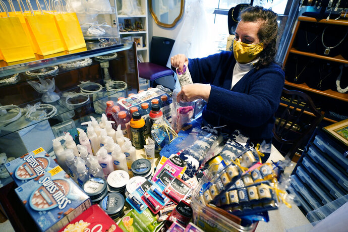 Volunteer Athena Papageorgiou prepares student care packages in her home, Tuesday, Nov. 17, 2020, in Ann Arbor, Mich. A group of parents has come together to help support University of Michigan students while they are sick or quarantining. The group of mostly moms was started and is organized by Sherry Levine of Rye Brook, New York, who's also a mother of a Michigan student. After she spread the word on parent pages on Facebook, local volunteers stepped up to help fulfill student requests by dropping off groceries or supplies. (AP Photo/Carlos Osorio)