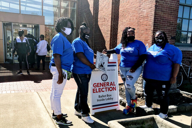 Breonna Taylor's mother, Tamika Palmer, second from right, stands in front of the Kentucky Center for African American Heritage, one of the four early voting locations in Louisville, Ky., Tuesday, Oct. 13, 2020. (AP Photo/ Piper Hudspeth Blackburn)