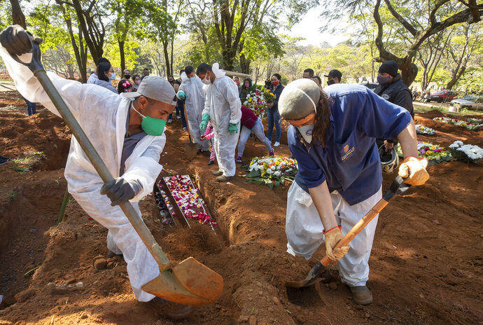Cemetery workers bury 65-year-old Maria Joana Nascimento, whose family members, behind, suspect died of COVID-19, at Vila Formosa cemetery in Sao Paulo, Brazil, Thursday, Aug. 6, 2020. Brazil is nearing 3 million cases of COVID-19 and 100,000 deaths. (AP Photo/Andre Penner)