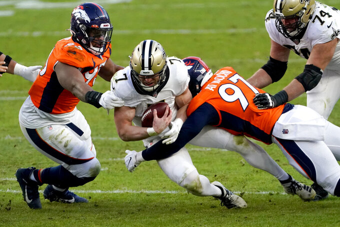 New Orleans Saints quarterback Taysom Hill (7) is tackled by Denver Broncos outside linebacker Jeremiah Attaochu (97) and defensive end Dre'Mont Jones during the second half of an NFL football game, Sunday, Nov. 29, 2020, in Denver. (AP Photo/Jack Dempsey)