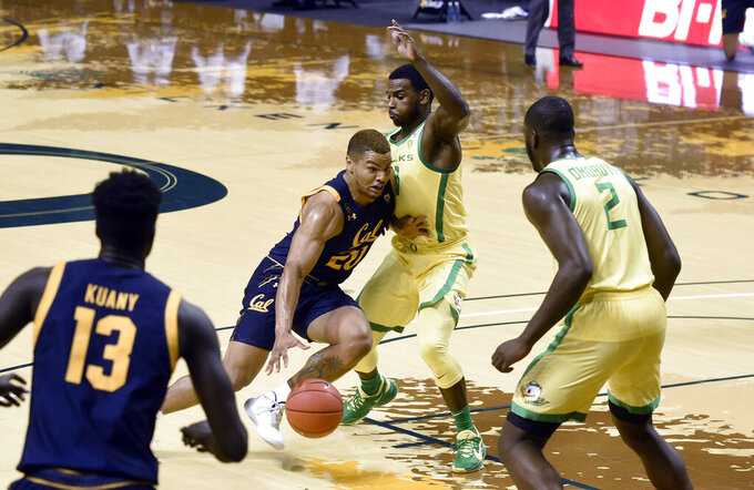 California guard Matt Bradley (20) drives the lane while being defended by Oregon guard Amauri Hardy (11) during the first half of an NCAA college basketball game in Eugene, Ore., Friday, Dec. 31, 2020. (AP Photo/Andy Nelson)