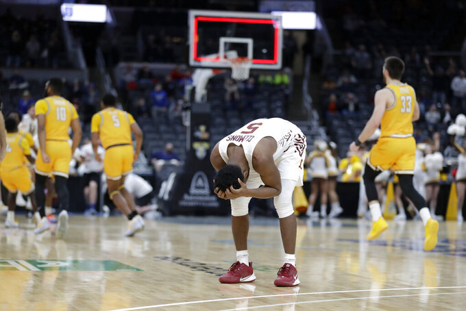 Loyola of Chicago's Keith Clemons (5) reacts as members of Valparaiso celebrate in the background following an NCAA college basketball game in the quarterfinal round of the Missouri Valley Conference men's tournament Friday, March 6, 2020, in St. Louis. Valparaiso won 74-73 in overtime. (AP Photo/Jeff Roberson)