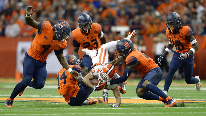 Clemson wide receiver Hunter Renfrow (13) is upended by Syracuse defensive back Evan Foster (14) and defensive back Jordan Martin (2) during the first half of an NCAA college football game, Friday, Oct. 13, 2017, in Syracuse, N.Y. (AP Photo/Adrian Kraus)