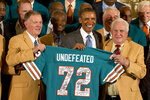 FILE - In this Aug. 20, 2013 file photo former Miami Dolphins football quarterback Bob Griese, left, President Barack Obama and 1972 Dolphins Coach Don Shula, right, hold a signed jersey in the East Room of the White House in Washington during a ceremony honoring the Super Bowl VII football Champion Miami Dolphins. The perfection of the 1972 Dolphins has earned them the nod as the NFL's greatest team. The 1972 Dolphins edged the 1985 Chicago Bears for the NFL's greatest team in balloting by 59 national media members as part of the NFL's celebration of its 100th season. (AP Photo/Jacquelyn Martin, file)