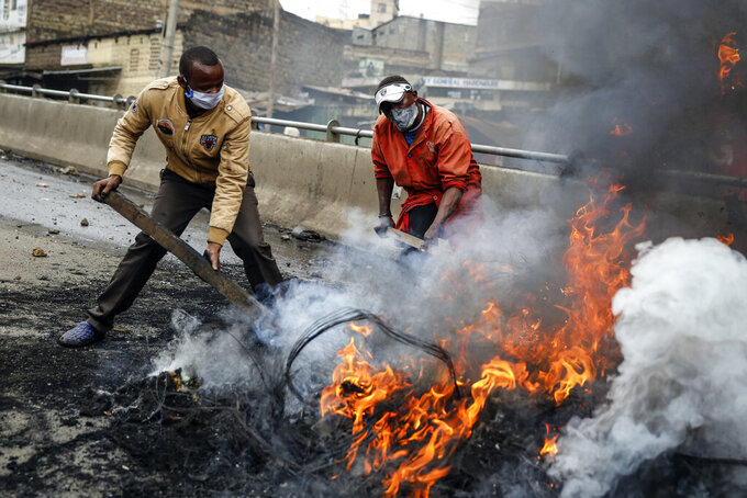 Residents put out a fire on a burning tyre barricade in the Kariobangi slum of Nairobi, Kenya Friday, May 8, 2020. Hundreds of protesters blocked one of the capital's major highways with burning tires to protest government demolitions of the homes of more than 7,000 people and the closure of a major food market, causing many to sleep out in the rain and cold because of restrictions on movement due to the coronavirus. (AP Photo/Brian Inganga)