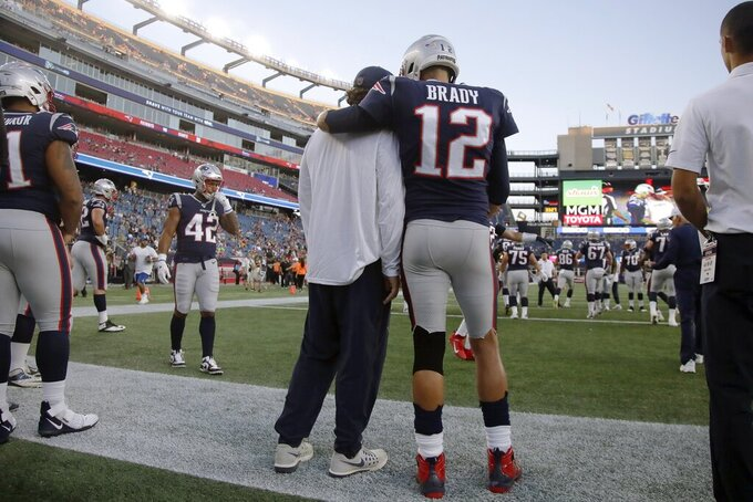 New England Patriots quarterback Tom Brady (12) stands with center David Andrews as the team warms up before an NFL preseason football game against the New York Giants, Thursday, Aug. 29, 2019, in Foxborough, Mass. (AP Photo/Elise Amendola)