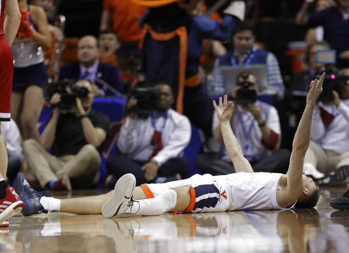 Virginia's Kyle Guy reacts after making a 3-point basket and being fouled during the second half of an NCAA college basketball game against North Carolina State in the Atlantic Coast Conference tournament in Charlotte, N.C., Thursday, March 14, 2019. (AP Photo/Chuck Burton)