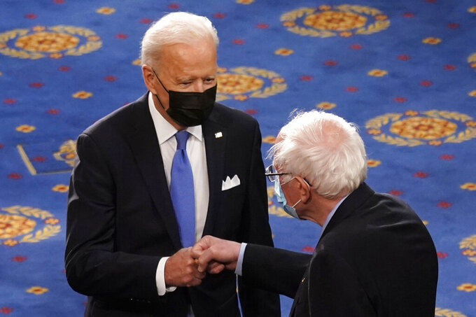 FILE - In this April 28, 2021 file photo, President Joe Biden greets Sen. Bernie Sanders, I-Vt., as Biden arrives to speak to a joint session of Congress  in the House Chamber at the U.S. Capitol in Washington. Many working-age people assume that Medicare covers just about every kind of health care that an older person may need. But it doesn't. Some of the biggest gaps involve dental, vision and hearing services. Now Democrats are trying to make those benefits a standard part of Medicare under massive legislation expected later this year to advance President Joe Biden's domestic agenda. Vermont Independent Sen. Bernie Sanders and other progressives are leading the push. (AP Photo/Andrew Harnik, Pool)