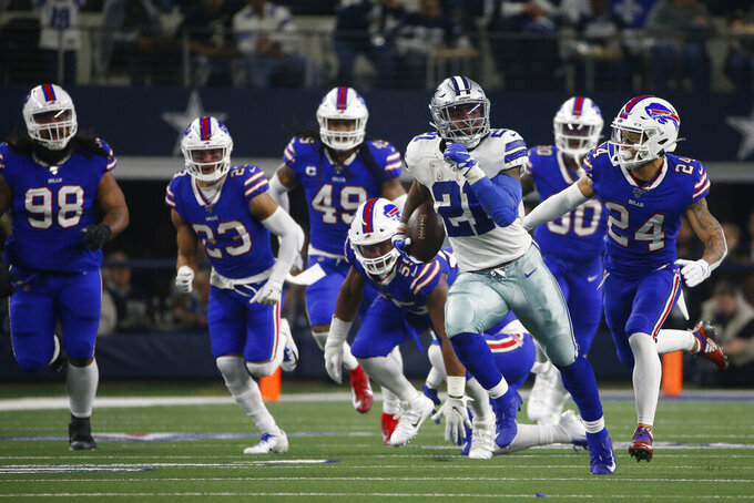 Dallas Cowboys running back Ezekiel Elliott (21) breaks out on a long run as Buffalo Bills defensive tackle Star Lotulelei (98), Micah Hyde (23) Tremaine Edmunds (49), Taron Johnson (24) and others give chase in the first half of an NFL football game in Arlington, Texas, Thursday, Nov. 28, 2019. (AP Photo/Ron Jenkins)