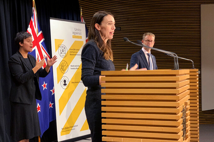 New Zealand's Prime Minister Jacinda Ardern, center, and Director-General of Health Ashley Bloomfield, right, talk to media in Wellington, New Zealand Monday, Feb. 15, 2021. As people in Auckland adjusted to a new lockdown on Monday, health officials said they'd found no evidence the coronavirus had spread further in the community, raising hopes the restrictions might be short-lived. (AP Photo/Nick Perry)