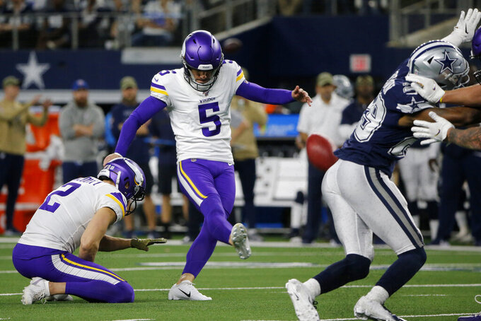 Minnesota Vikings' Britton Colquitt (2) holds as Dan Bailey (5) kicks an extra point during the first half of the team's NFL football game against the Dallas Cowboys in Arlington, Texas, Sunday, Nov. 10, 2019. (AP Photo/Michael Ainsworth)