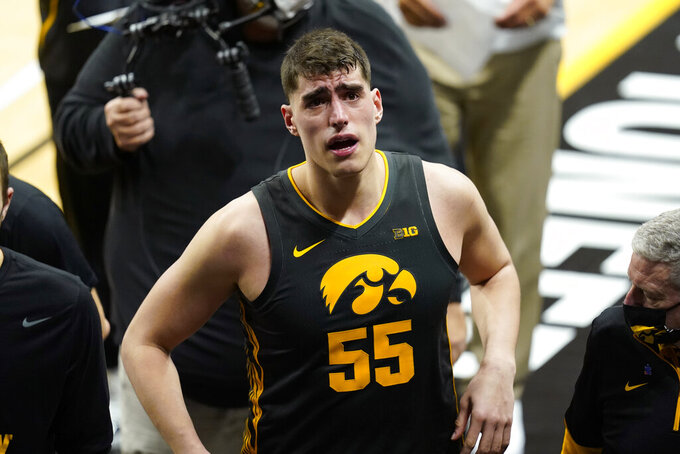 Iowa center Luka Garza walks off the court after an NCAA college basketball game against Wisconsin, Sunday, March 7, 2021, in Iowa City, Iowa. Garza, a senior, was playing his last home game at Iowa. Iowa won 77-73. (AP Photo/Charlie Neibergall)