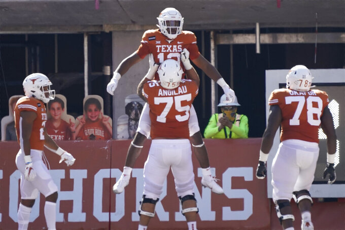 Texas' Brennan Eagles (13) celebrates his touchdown catch against West Virginia with Junior Angilau (75) during the first half of an NCAA college football game in Austin, Texas, Saturday, Nov. 7, 2020. (AP Photo/Chuck Burton)