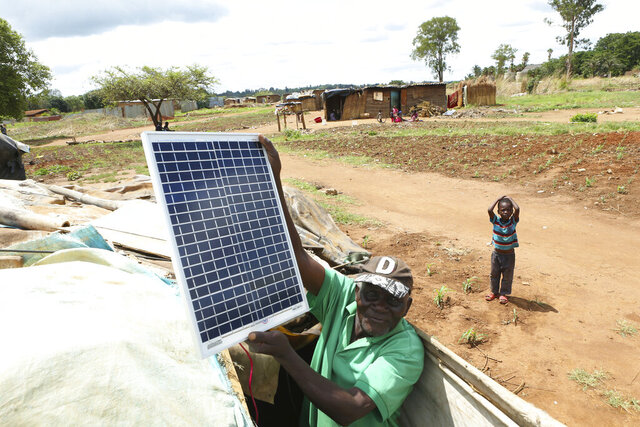 In this Thursday, Dec. 12, 2019 photo, Chiwenga Mutekede, 78, displays his solar panel perched atop a makeshift shack made from plastics sheets, cardboard boxes, grass and mud in a squatter camp in Harare. With no sign of the state utility generating adequate electricity, desperate Zimbabweans are reverting to a combination of old and new sources of energy: firewood for cooking and solar for light. (AP Photo/Tsvangirayi Mukwazhi)