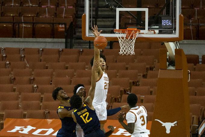 Texas forward Jericho Sims (20) goes up to block the shot of West Virginia guard Taz Sherman (12) during the second half of an NCAA college basketball game, Saturday, Feb. 20, 2021, in Austin, Texas. (AP Photo/Michael Thomas)