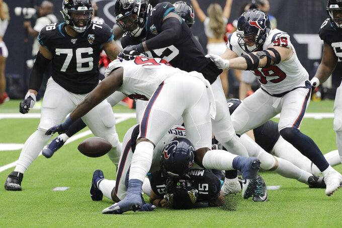 Jacksonville Jaguars quarterback Gardner Minshew (15) fumbles as he is hit by Houston Texans outside linebacker Whitney Mercilus (59) during the second half of an NFL football game Sunday, Sept. 15, 2019, in Houston. (AP Photo/David J. Phillip)