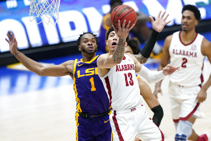 Alabama's Jahvon Quinerly (13) drives against LSU's Ja'Vonte Smart (1) during the first half of the championship game at the NCAA college basketball Southeastern Conference Tournament Sunday, March 14, 2021, in Nashville, Tenn. (AP Photo/Mark Humphrey)