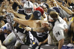 Fans in The Black Hole reach out to mob Oakland Raiders running back Josh Jacobs after he scored a touchdown during the fourth quarter of an NFL football game against the Denver Broncos Monday, Sept. 9, 2019, in Oakland, Calif. (AP Photo/Ben Margot)