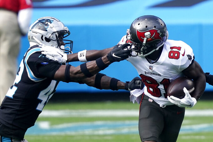 Carolina Panthers safety Sam Franklin (42) grabs Tampa Bay Buccaneers wide receiver Antonio Brown (81) by the facemask during the first half of an NFL football game, Sunday, Nov. 15, 2020, in Charlotte , N.C. (AP Photo/Gerry Broome)