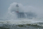 Waves crash over the harbour and a lighthouse, as Storm Ciara hits Newhaven, on the south coast of England, Sunday, Feb. 9, 2020. Trains, flights and ferries have been cancelled and weather warnings issued across the United Kingdom and in northern Europe as the storm with winds expected to reach hurricane levels batters the region. (AP Photo/Matt Dunham)