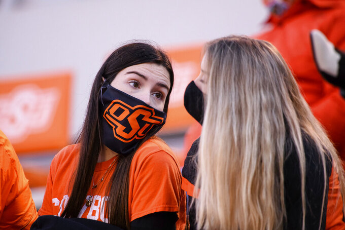 Masked Oklahoma State fans visit during a timeout at the end of an NCAA college football game against Iowa State, Saturday, Oct. 24, 2020, in Stillwater, Okla. (AP Photo/Brody Schmidt)