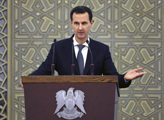 In this photo released by the Syrian official news agency SANA, Syrian President Bashar Assad speak during meeting with heads of local councils from all Syrian provinces, in Damascus, Syria, Sunday, Feb. 17, 2018. Assad said that only the Syrian army can protect groups in northern Syria. In a speech he appeared to be referring to U.S.-allied Kurdish groups, which fear a Turkish assault once American troops withdraw from northeastern Syria. (SANA via AP)