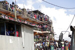 People watch as rescue workers attend the scene of a building that collapsed in Tasia Embakasi, an east neighbourhood of Nairobi, Kenya on Friday Dec. 6, 2019. A six-story building collapsed in Kenya's capital on Friday, officials said, with people feared to be trapped in the debris. Police say people have been rescued by residents using their bare hands. (AP Photo/Khalil Senosi)