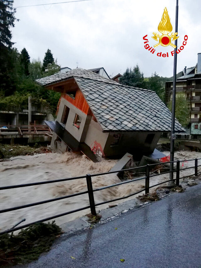 A building is toppled over by the Cervo river in spate due to heavy rains in Biella, northern Italy, Saturday, Oct. 3, 2020.     (Firefighter Vigili del Fuoco via AP)
