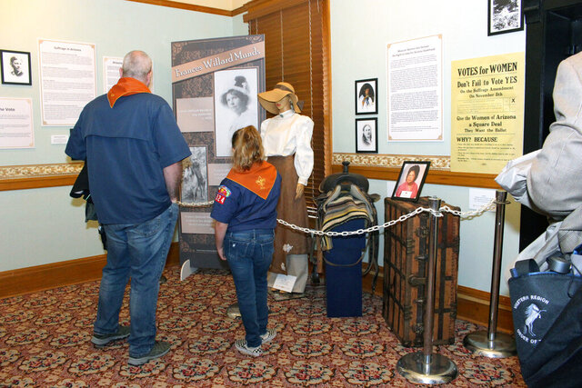 Visitors to the Arizona Capitol Museum look at a display honoring the state's early suffrage movement in this Wednesday, March 11, 2020, in Phoenix. The display includes a mannequin dressed in period consume depicting Frances Willard Munds, who led a successful 1912 ballot initiative that gave women the right to vote. (AP Photo/Bob Christie)