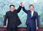 FILE - In this April 27, 2018, file photo, North Korean leader Kim Jong Un, left, and South Korean President Moon Jae-in raise their hands after signing on a joint statement at the border village of Panmunjom in the Demilitarized Zone, South Korea. Kim's fifth meeting with Chinese President Xi Jinping continues his ambitious diplomatic outreach that has included summits with the leaders of the United States, South Korea and Russia in the past year and a half. Experts say Kim is attempting to form a united front with North Korea's main ally China to strengthen his leverage in the stalled nuclear negotiations with the United States. (Korea Summit Press Pool via AP, File)