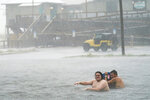 People play in a flooded parking lot at Navarre Beach, Tuesday, Sept. 15, 2020, in Pensacola Beach, Fla. Hurricane Sally is crawling toward the northern Gulf Coast at just 2 mph, a pace that's enabling the storm to gather huge amounts of water to eventually dump on land. (AP Photo/Gerald Herbert)