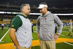 FILE - In this Nov. 16, 2019, file photo, Baylor head coach Matt Rhule, left, and Oklahoma head coach Lincoln Riley talk at midfield prior to an NCAA college football game in Waco, Texas. Rhule and Riley took over their teams under drastically different circumstances. Now they will coach against each other in the Big 12 championship game. (AP Photo/Ray Carlin, File)
