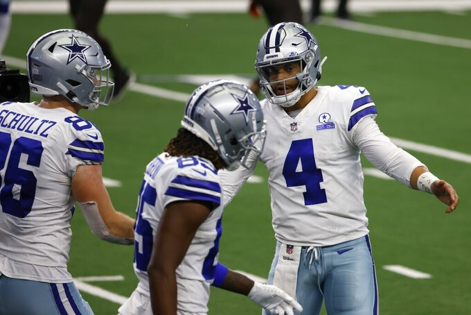 Dallas Cowboys' Dalton Schultz (86), Noah Brown (85) and Dak Prescott (4) celebrate Schultz's touchdown catch in the second half of an NFL football game against the Cleveland Browns in Arlington, Texas, Sunday, Oct. 4, 2020. (AP Photo/Ron Jenkins)