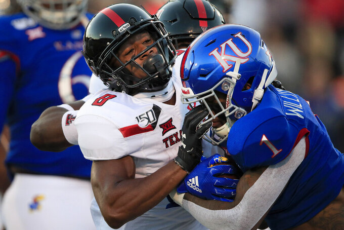 Texas Tech defensive back Zech McPhearson (8) stops Kansas running back Pooka Williams Jr. (1) during the first half of an NCAA college football game in Lawrence, Kan., Saturday, Oct. 26, 2019. (AP Photo/Orlin Wagner)