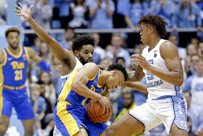 North Carolina guard Jeremiah Francis, left, and forward Armando Bacot (5) guard Pittsburgh guard Trey McGowens (2) during the first half of an NCAA college basketball game in Chapel Hill, N.C., Wednesday, Jan. 8, 2020. (AP Photo/Gerry Broome)