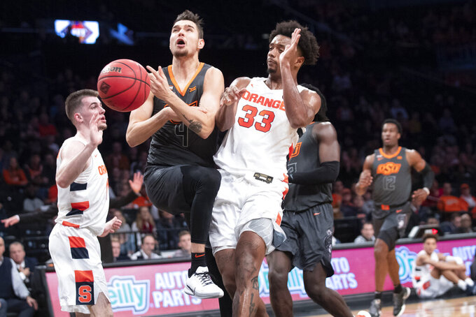 Syracuse forward Elijah Hughes (33) fouls Oklahoma State guard Thomas Dziagwa (4) during the first half of an NCAA college semi final basketball game in the NIT Season Tip-Off tournament, Wednesday, Nov. 27, 2019, in New York. (AP Photo/Mary Altaffer)