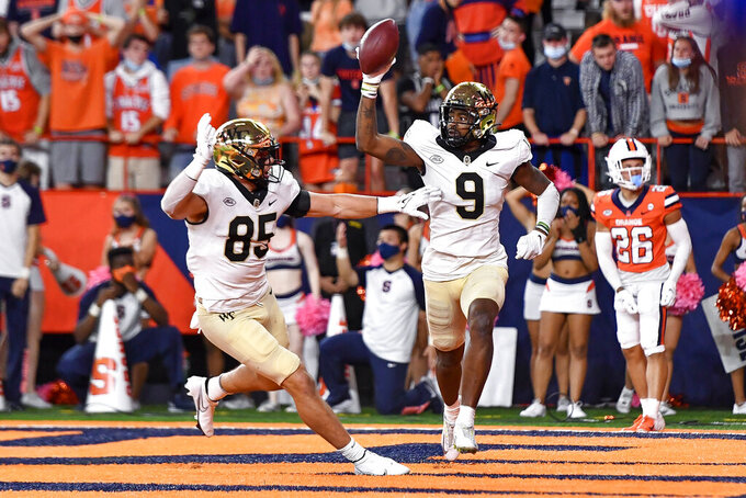 Wake Forest wide receiver A.T. Perry (9) celebrates with tight end Blake Whiteheart (85) after scoring a touchdown during overtime of an NCAA college football game against Syracuse in Syracuse, N.Y., Saturday, Oct. 9, 2021. Wake Forest beat Syracuse 40-37. (AP Photo/Adrian Kraus)