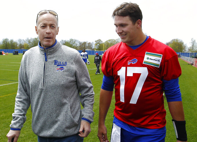 "FILE - In this May 11, 2018, file photo, Buffalo Bills rookie quarterback Josh Allen (17) walks with Hall of Fame quarterback Jim Kelly following the team's NFL football rookie minicamp in Orchard Park, N.Y. Kelly has made a point of keeping his distance by limiting his chats with Allen via text for much of this year. Kelly's decision has less to do with the coronavirus pandemic as it does Kelly not wanting to distract the third-year starter. ""He doesn't need me in his ear, so I pretty much leave him alone,"" Kelly told The Associated Press. (AP Photo/Jeffrey T. Barnes, File)"