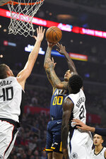 Utah Jazz guard Jordan Clarkson (00) shoots as Los Angeles Clippers center Ivica Zubac, left, and guard Patrick Beverley defend during the first half of an NBA basketball game Saturday, Dec. 28, 2019, in Los Angeles. (AP Photo/Mark J. Terrill)
