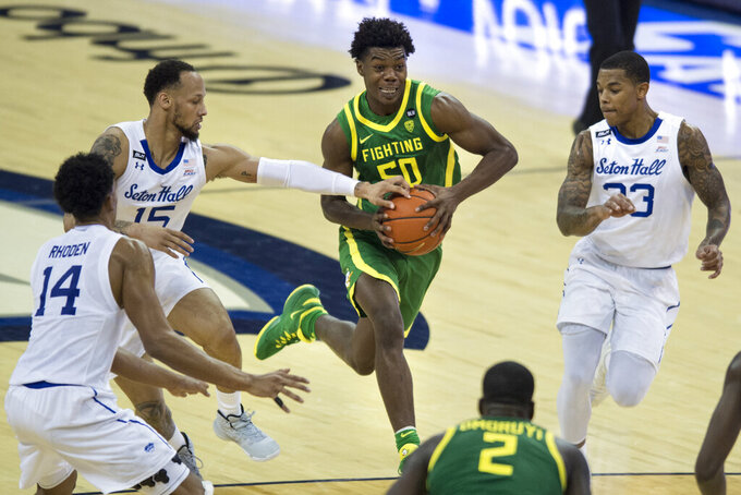 Oregon's Eric Williams Jr. drives to the basket between coverage by Seton Hall's Takal Molson, left, and Shavar Reynolds Jr., right, during the second half of an NCAA college basketball game in Omaha, Neb., Friday, Dec. 4, 2020. (AP Photo/Kayla Wolf)