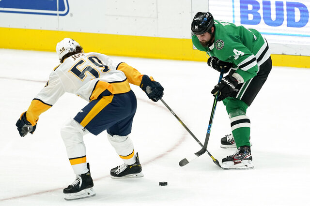Nashville Predators defenseman Roman Josi (59) and Dallas Stars left wing Jamie Benn (14) compete for control of the puck in the first period of an NHL hockey game in Dallas, Friday, Jan. 22, 2021. (AP Photo/Tony Gutierrez)