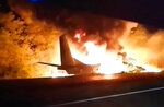 In this TV grab released by Ukraine's Emergency Situation Ministry, an AN-26 military plane bursts into flames after it crashed in the town of Chuguyiv close to Kharkiv, Ukraine, late Friday, Sept. 25, 2020. Among 28 people on board 22 people were killed. (Emergency Situation Ministry via AP)