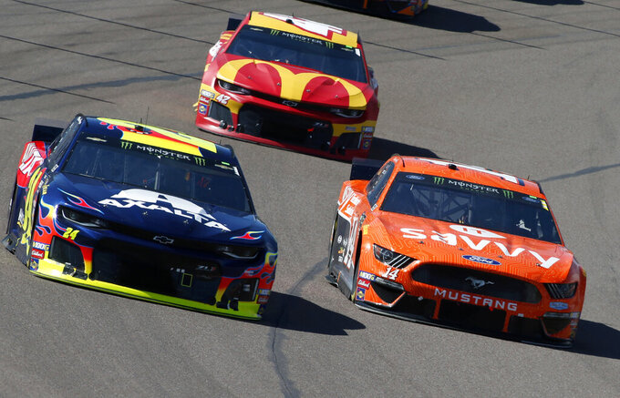 William Byron (24) and Clint Bowyer (14) race out of Turn 4 during the NASCAR Cup Series auto race at ISM Raceway, Sunday, March 10, 2019, in Avondale, Ariz. (AP Photo/Ralph Freso)