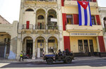 Special forces police patrol the streets as they drive past a large Cuban flag hanging from the facade of a building, in Havana, Cuba, Wednesday, July 21, 2021. (AP Photo/Eliana Aponte)