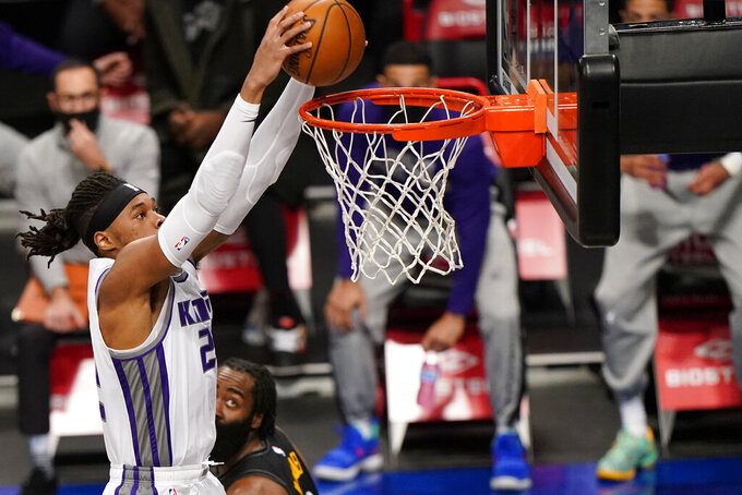 Sacramento Kings center Richaun Holmes, left, dunks the ball as Brooklyn Nets guard James Harden, right,  looks on from the floor during the first quarter of an NBA basketball game, Tuesday, Feb. 23, 2021, in New York. (AP Photo/Kathy Willens)
